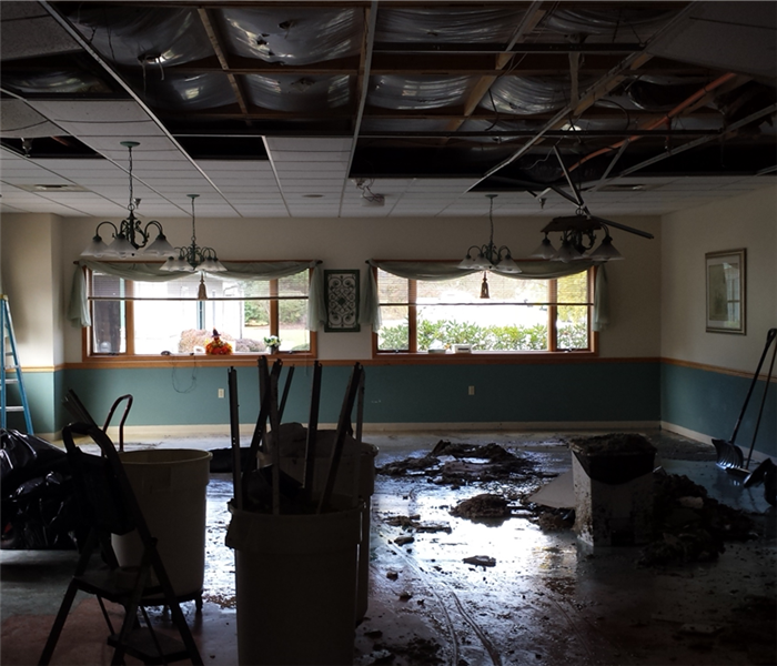 A commercial dining room that experienced water damage from a pipe break. The ceiling is down and the room wet.