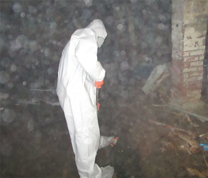 A SERVPRO employee cleaning a sewer backup in full personal protective equipment.