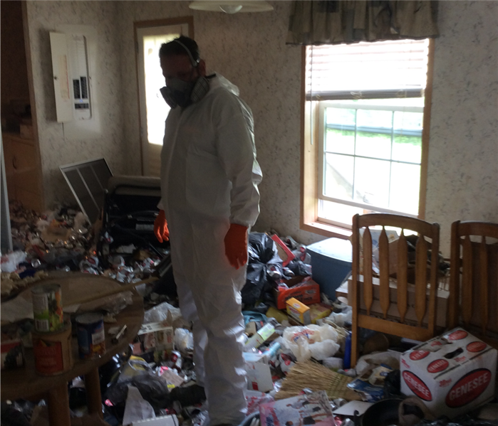 A SERVPRO employee in full personal protective equipment inside a hoarding home in Hamlin, Pa