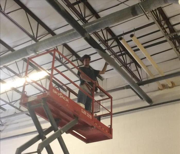 A SERVPRO employee in a sicissor lift cleaning dust from a rafter at a Scranton plastic manufacturer.
