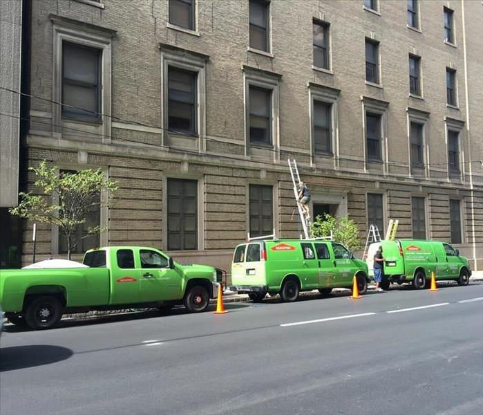A picture of several SERVPRO trucks lined up on a Scranton street address a commercial disaster