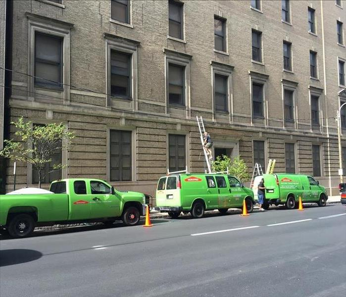 SERVPRO trucks parked next to a tall commercial building where we were working