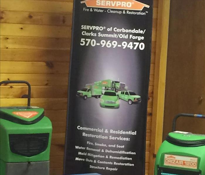 A picture of the SERVPRO logo/banner with some of our equipment in our Lackawanna County facility.
