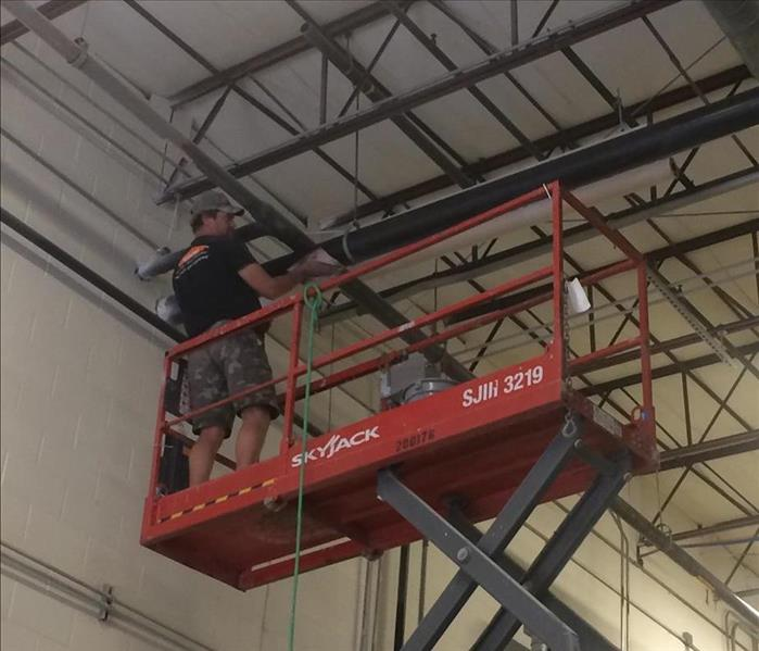 A SERVPRO employee in a scissor lift cleaning a high ceiling at a local manufacturing facility