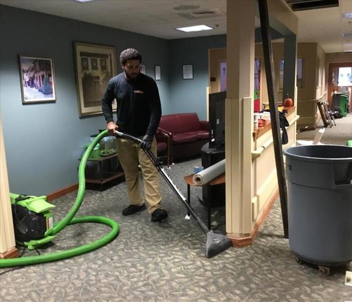 SERVPRO employee using our extracting equipment to suck water from a carpet