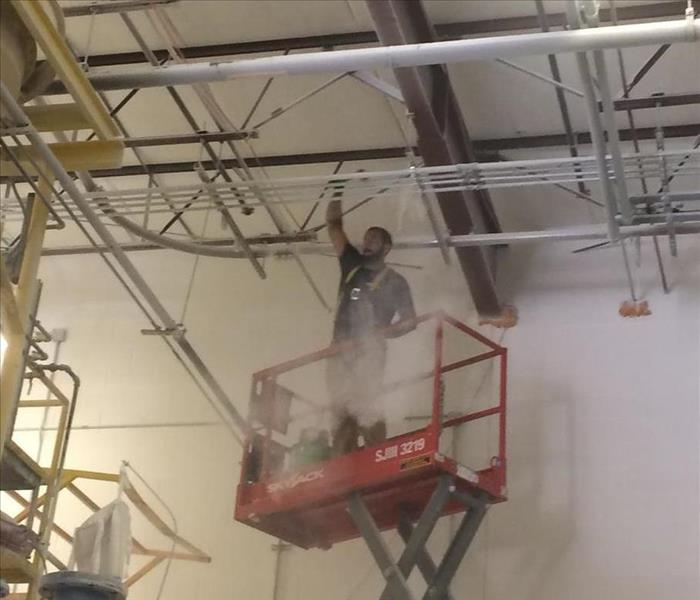 A SERVPRO employees in a scissor lift cleaning a high ceiling
